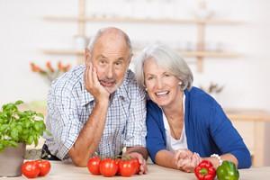 lächelndes älteres ehepaar in der küche
