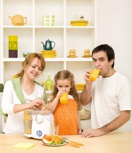 Family making and drinking fresh fruit juice