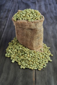 Green coffee beans in burlap sack on old wooden table