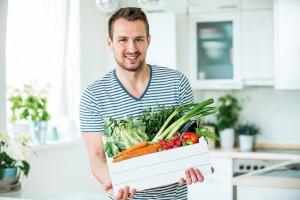 Junger Mann mit Gemüsekiste in der Küche