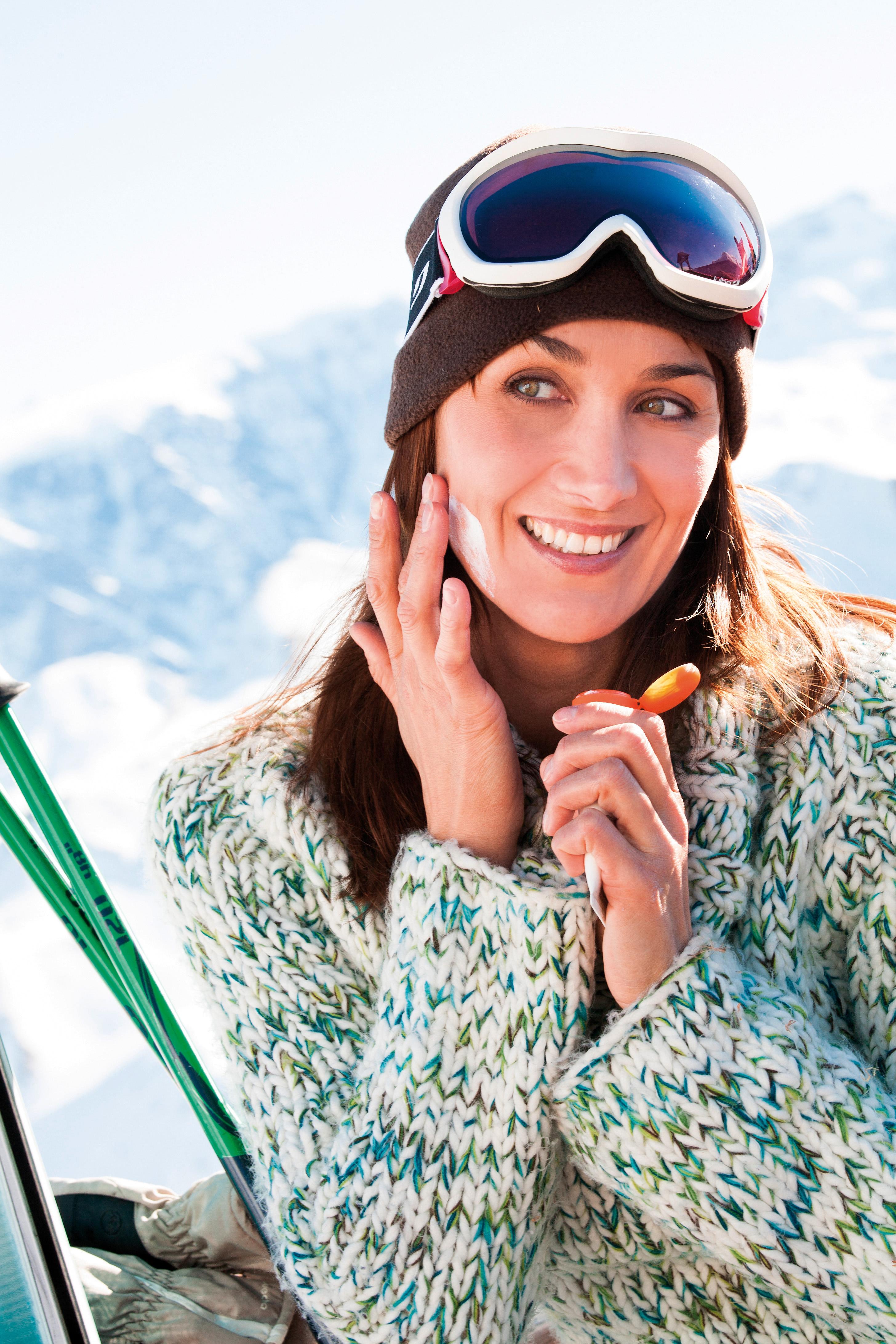 portrait d'une belle femme souriante se mettant de la crme de pr