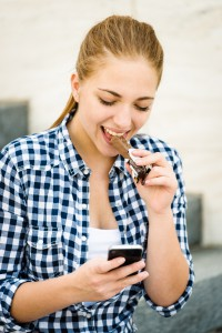 Teenager eating chcolate looking in phone