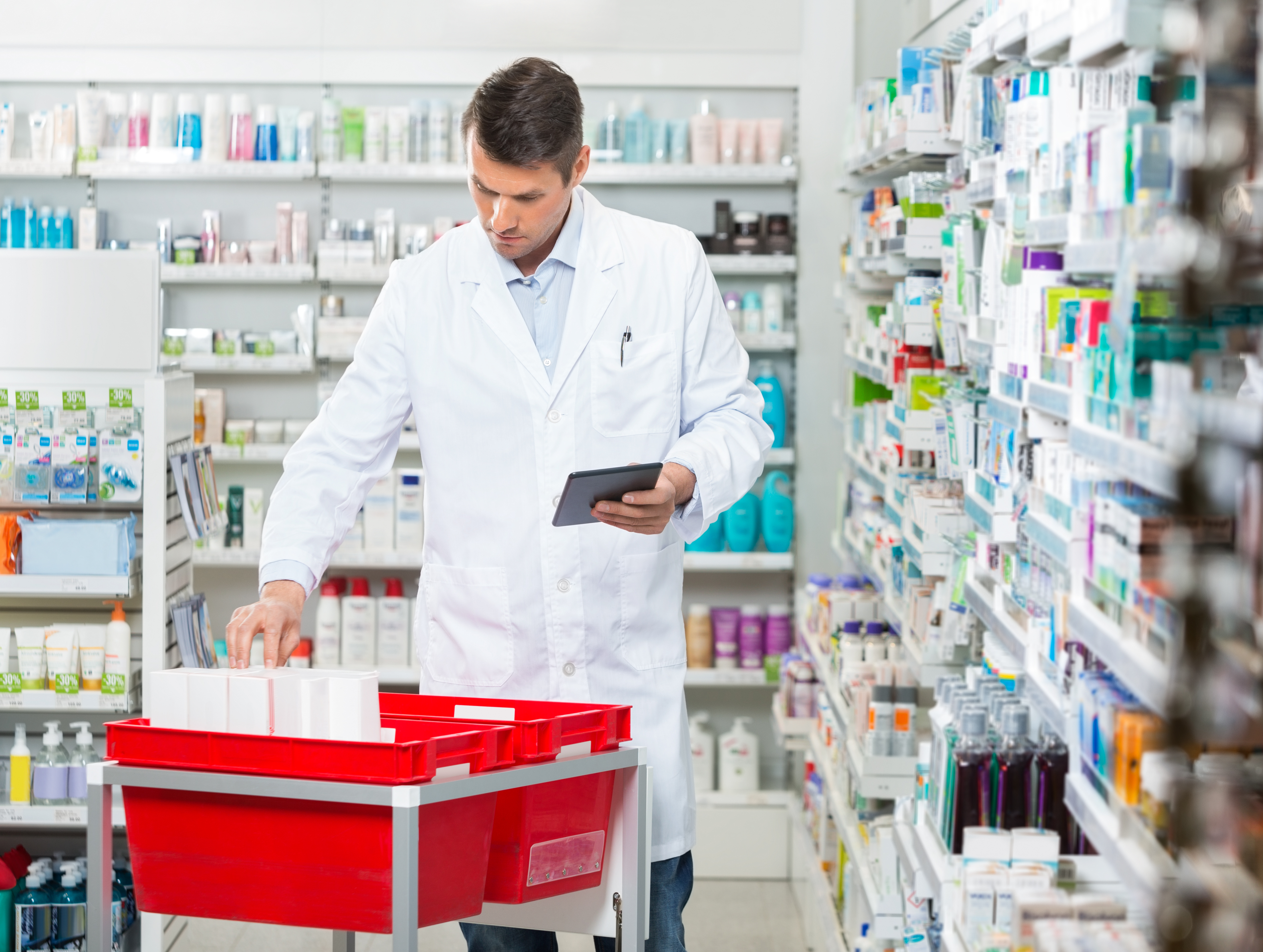 Mid adult male pharmacist counting stock while holding digital tablet at drugstore