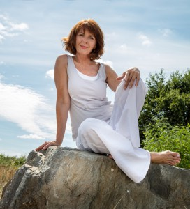 senior zen - smiling, beautifully aging woman sitting on a stone for outdoors yoga session wearing white seeking serenity and wellness in a park,summer daylight