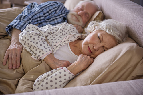 Tranquil married couple lying in bed and sleeping. Old husband i