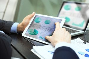 Business person analyzing financial statistics displayed on the