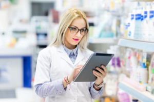 Pharmacy details - blonde doctor in white uniform using tablet a