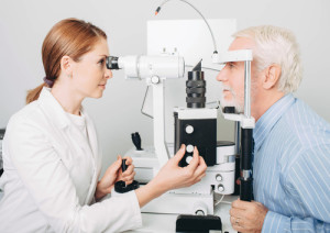 Senior patient checking vision with special eye equipment