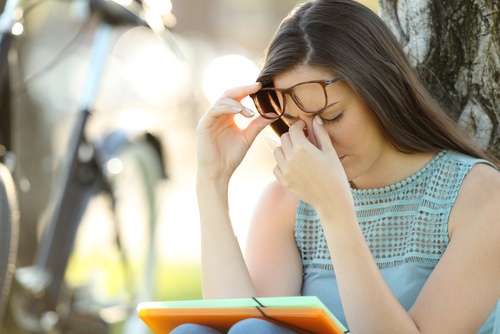 Student suffering eyestrain while is studying