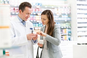 Pharmacist and customer reviewing prescription label in pharmacy